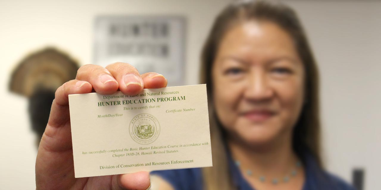 Hunter Education staff holding a certification card.