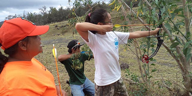 Bowhunter instructor helping a teenage girl and adult male who each is holding bow and arrow.